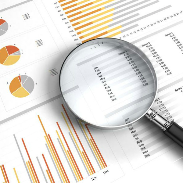 Magnifying glass looking at statistics report